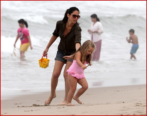 Olivia munn plays in the sand with her family